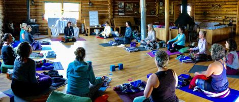 People sitting on yoga mats in a rustic cabin