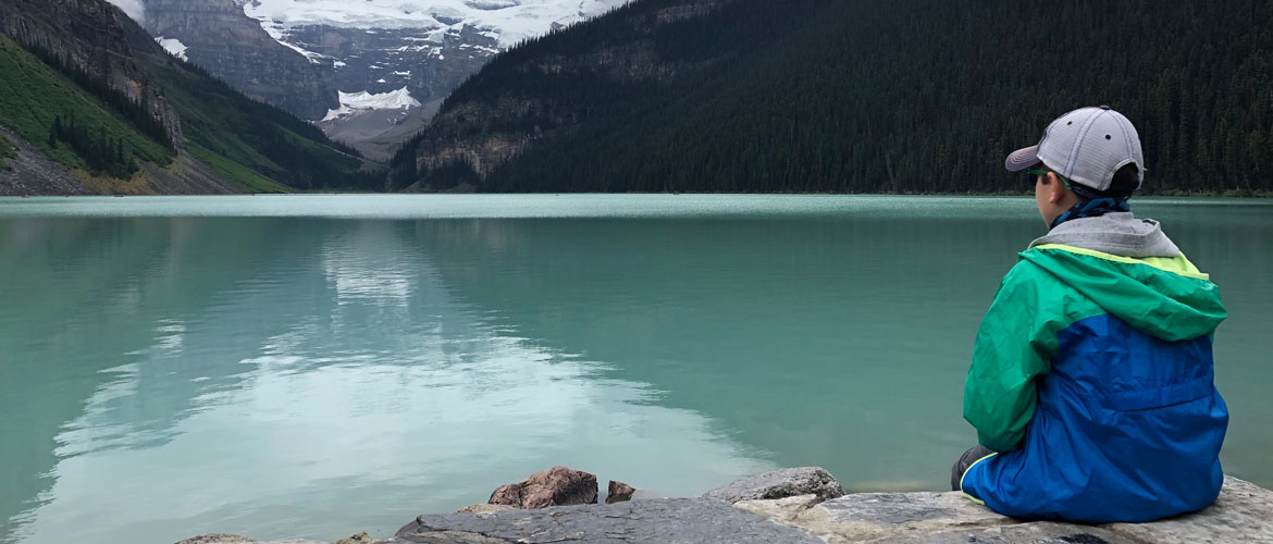 kid sitting on a rock looking at a mountain lake