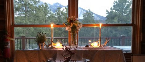 candles, flowers, antlers on a table with a mountain backdrop through the window