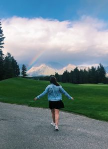person walking on a path towards a rainbow